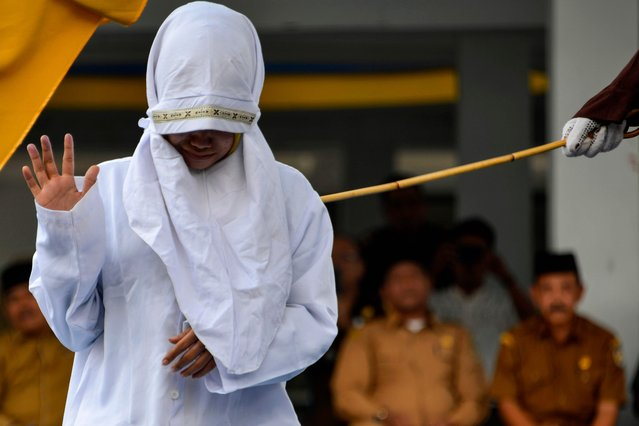 A woman reacts as she is caned in public by a member of the Sharia police in Banda Aceh on March 2, 2020. Aceh is the only region in the world's biggest Muslim-majority nation that imposes Islamic law – known as Sharia – with those found guilty of breaches often publicly whipped with a rattan cane. (Photo by Chaideer Mahyuddin/AFP Photo)
