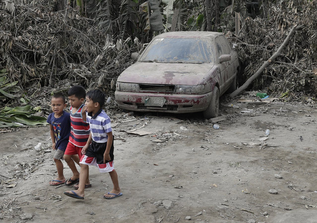 Boys pass by a car that is covered in volcanic-ash at a town near Taal volcano in Tagaytay, Cavite province, southern Philippines on Sunday January 19, 2020. (Photo by Aaron Favila/AP Photo)