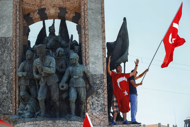 People protesting against the coup, wave a Turkish flag on top of the monument in Taksim square, Istanbul, Turkey, Saturday, July 16, 2016. (Photo by Emrah Gurel/AP Photo)