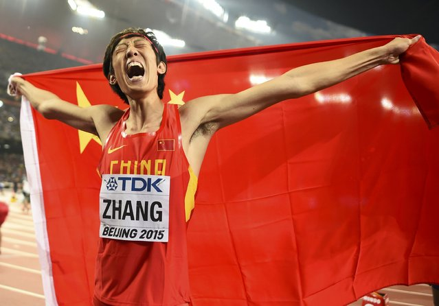 Second placed Zhang Guowei of China celebrates with a national flag after winning silver in the men's high jump final during the 15th IAAF World Championships at the National Stadium in Beijing, China, August 30, 2015. (Photo by Dylan Martinez/Reuters)