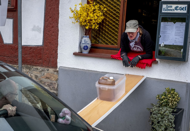 """A can with apple cider slides down to car from a window of the apple cider restaurant """"Zum Lahmen Esel"""" in Frankfurt, Germany, Friday, April 3, 2020. Due to the coronavirus outbreak the restaurant which has been in operation since 1807 offers cider and food to go in a self-made drive through set up. (Photo by Michael Probst/AP Photo)"""