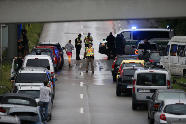 Police halt traffic on a road near to the scene of a shooting rampage at the Olympia shopping mall in Munich, Germany July 22, 2016. (Photo by Michael Dalder/Reuters)