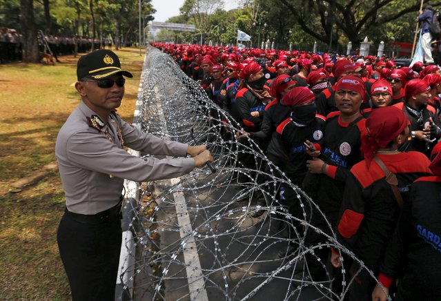 Central Jakarta police chief Hendro Pandowo stands next to razor wire as Indonesian trade union workers hold a protest outside the Presidential Palace in Jakarta September 1, 2015. Thousands of workers protested on Tuesday against job cuts and called for higher wages, raising pressure on the government as it struggles to kickstart an economy growing at its slowest in six years. (Photo by Reuters/Beawiharta)