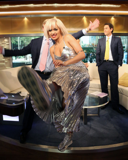 """Steve Doocy and Clayton Morris photobomb Rita Ora as she visits """"Fox & Friends"""" at the FOX Studios on August 19, 2014 in New York City. (Photo by Taylor Hill/Getty Images)"""