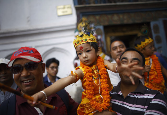 A boy dressed as Lord Krishna participates in a parade to mark the Gaijatra Festival, also known as the festival of cows, in Kathmandu August 11, 2014. (Photo by Navesh Chitrakar/Reuters)