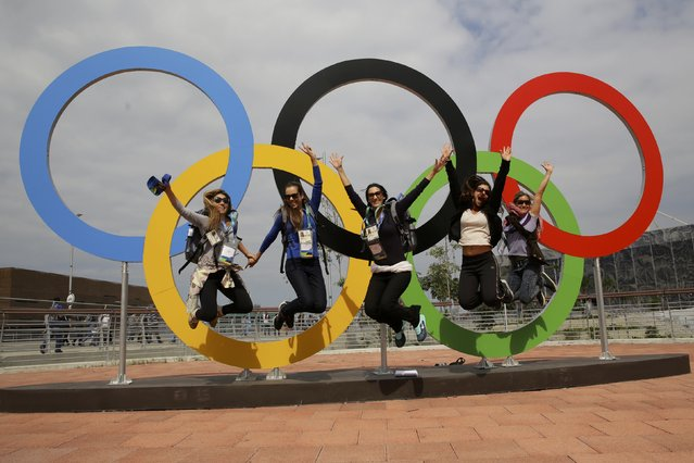 Hospitality staff from Visa pose as they jump next to the Olympic rings inside the Olympic Park in Rio de Janeiro, Brazil on July 30, 2016. (Photo by Kevin Coombs/Reuters)