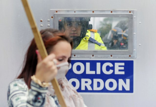 A police officer looks at demonstrators through a window in a security screen during the NATO summit at the Celtic Manor resort, near Newport, in Wales September 4, 2014. The resort is the venue for the two day NATO summit which started today. (Photo by Suzanne Plunkett/Reuters)