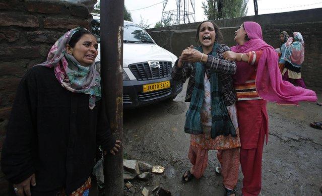 Kashmiri women wail as they stand near their submerged houses in Srinagar, India, Sunday, September 7, 2014. (Photo by Mukhtar Khan/AP Photo)