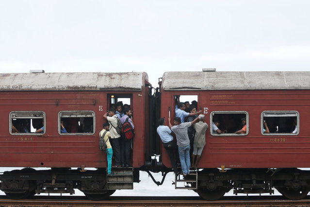 Commuters travel to work by train in Colombo, Sri Lanka on June 13, 2017. (Photo by Dinuka Liyanawatte/Reuters)