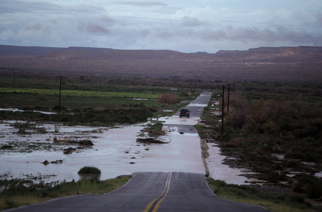 A truck crosses floodwaters on a road in Moapa, Nev., Monday, September 8, 2014. Flooding throughout the area damaged homes and roads. (Photo by John Locher/AP Photo)