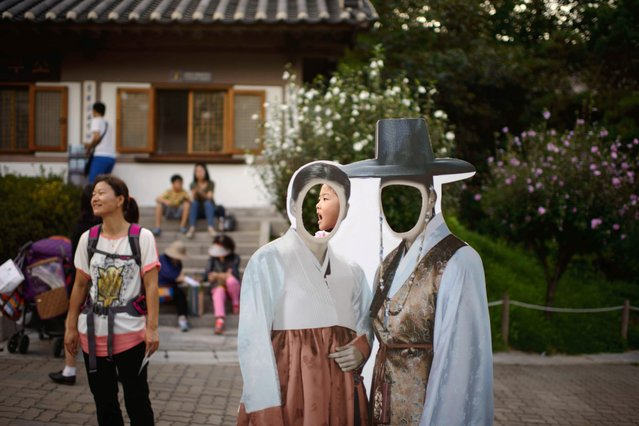 A child waits to pose behind cutouts featuring traditional Korean Hanbok costumes at a park during the Chuseok holiday period, in Seoul on September 9, 2014. During the Chuseok holiday many South Koreans return to their hometowns to celebrate the harvest season with their families. According to the Ministry of Land, Infrastructure and Transport, a total of 39.45 million travellers are expected to be on the move during the holiday period. (Photo by Ed Jones/AFP Photo)