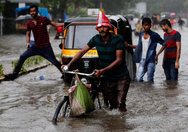 A man pushes his bicycle on a flooded road during heavy rains in Mumbai, India, August 5, 2016. (Photo by Shailesh Andrade/Reuters)