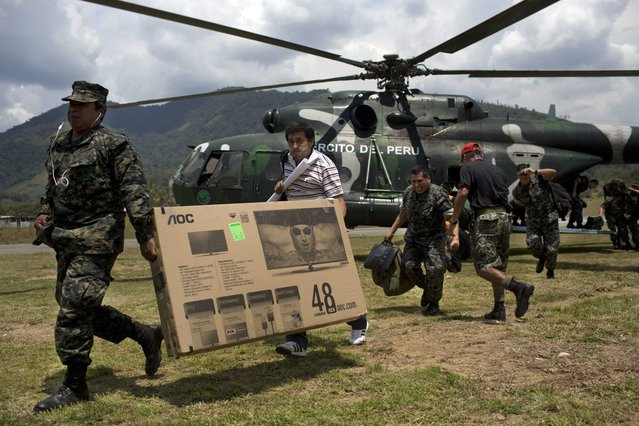 In this, September 19, 2014 photo, soldiers carry a TV after descending from a helicopter at  Mazamari anti drugs military base in the Apurimac, Ene and Mantaro River Valleys, or VRAEM, the world's No. 1 coca-growing region, in Junin, Peru. According to authorities an average of about  4-5 small planes daily fly into Peru from Bolivia, picking up about 300 kilos each of coca paste worth about a third of a million dollars in Bolivia, where it is further refined. (Photo by Rodrigo Abd/AP Photo)