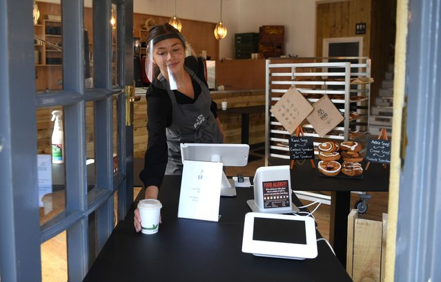 A shop assistant serves a takeaway Flat White coffee whilst wearing a safety visor at Brod Danish bakery and coffee shop on June 05, 2020 in Penarth, Wales. The British government further relaxed Covid-19 quarantine measures in England this week, allowing groups of six people from different households to meet in parks and gardens, subject to social distancing rules but under Welsh lockdown rules two separate households can meet outdoors maintain social distancing only if you stay in your local area. (Photo by Stu Forster/Getty Images)