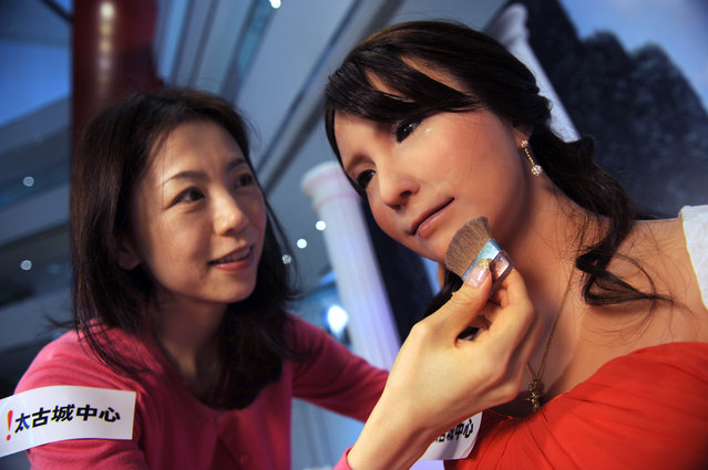 "Akie Koh, a stylist from Japan, makes final preparations on the face of Geminoid F, a female robot, in Hong Kong, on March 28, 2012. The Geminoid F robot, developed by Ishiguro Laboratory in Osaka University and ATR Intelligent Robotics and Communication Laboratories, will be on display with other robots at City Plaza's ""Robots in Motion 2012"" exhibition from March 29 to April 15. (Photo by Antony Dickson/AFP Photo)"