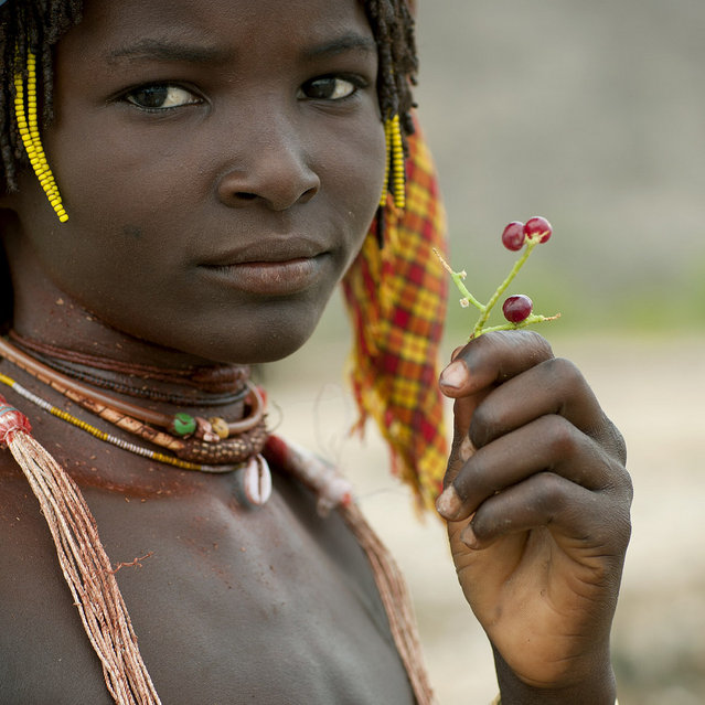 """Mucubal tribe girl – Angola. Mucubal like to eat this kind of cranberries. They boil them. To know if the water is hot enough, she put her hand inside. Once it really hurts, she throw the Cranberries inside. After 1 minute, they eat them. It is like eating some red pepper!"". (Eric Lafforgue)"
