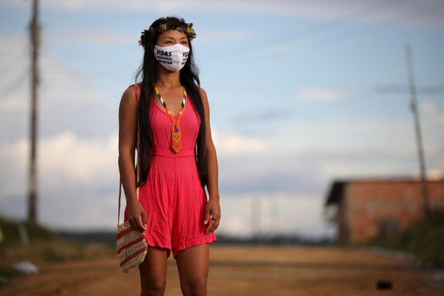 """Vanderlecia Ortega dos Santos, 32, a nurse from the Witoto tribe, an indigenous ethnic group, who has volunteered to provide the only frontline care protecting her indigenous community of 700 families from the COVID-19 outbreak, wears a face mask that reads """"Indigenous lives matter"""" as she poses for a photo outside, near her home in Parque das Trios, during the coronavirus disease (COVID-19) outbreak, in the Taruma district, Manaus, Brazil, May 3, 2020. """"Our people are dying from this disease here and they are not being recognized as indigenous people by the state and Sesai"""", said Santos. (Photo by Bruno Kelly/Reuters)"""