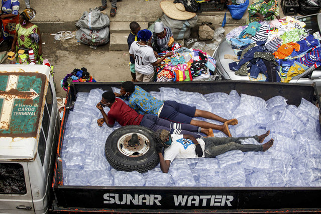 Men sleep on top of packets of sachet water arranged in a truck driven through a market in Mafoluku district, Lagos, Nigeria, 20 May 2020. With Lagos as the epicentre of the coronavirus disease in Nigeria, the most populous country in Africa has a record of 6,401 confirmed cases of the coronavirus, according the data shown on the Nigeria Centre for Disease Control website on 20 May 2020. (Photo by Akintunde Akinleye/EPA/EFE/Rex Features/Shutterstock)