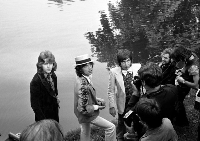 Mick Jagger, center, lead singer of The Rolling Stones pop music group, dons a straw hat as he and guitarist Mick Taylor and drummer Charlie Watts, right in bow tie, during a press conference at the Bois de Boulogne in Paris, France on September 22, 1970. (Photo by AP Photo)