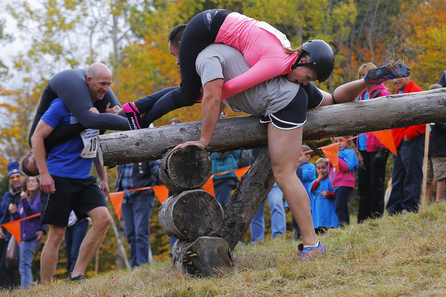 Shane Arnold and Brandy Bates clear the second obstacle ahead of Ian and Susan Bell (L) while competing in the North American Wife Carrying Championship at Sunday River ski resort in Newry, Maine October 11, 2014. REUTERS/Brian Snyder