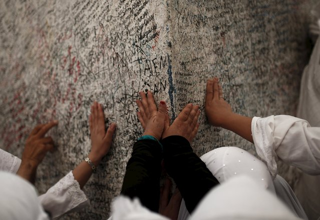 Muslim pilgrims touch a rock atop Mount Mercy on the plains of Arafat during the annual haj pilgrimage, outside the holy city of Mecca September 22, 2015. (Photo by Ahmad Masood/Reuters)