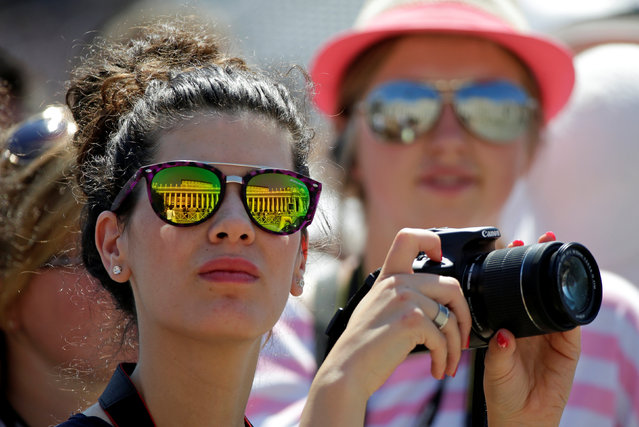 A woman looks on while holding a camera during the Angelus player led by Pope Francis in Saint Peter's Square at the Vatican August 28, 2016. (Photo by Max Rossi/Reuters)