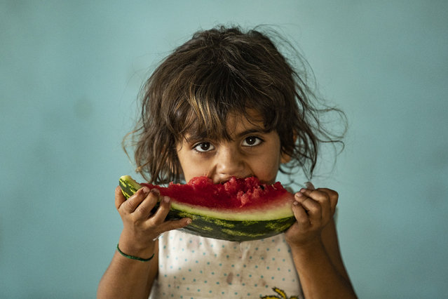 A girl eats a watermelon slice while at a school building where Syrians – displaced from the area of Ras al-Ain by the Turkish offensive on the northeast – are staying in the city of Hasakah, on June 30, 2020. (Photo by Delil Souleiman/AFP Photo)