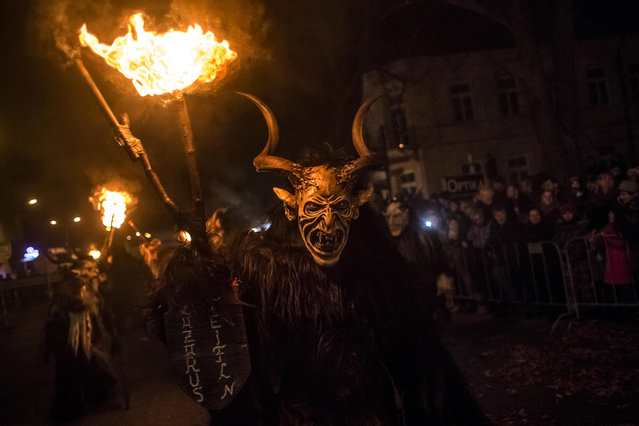 Participants dressed as the Krampus creatures walk the streets during Krampus gathering on December 12, 2015 in Kaplice, Czech Republic. Krampus, also called Tuifl or Perchten, is a demon-like creature represented by a fearsome, hand-carved wooden mask with animal horns, a suit made from sheep or goat skin and large cow bells attached to the waist that the wearer rings by running or shaking his hips up and down. Krampus has been a part of Central European, alpine folklore going back at least a millennium, and since the 17th-century Krampus traditionally accompanies St. Nicholas and angels on the evening of December 5 to visit households to reward children that have been good while reprimanding those who have not. However, in the last few decades the western Austrian region of Tyrol in particular has seen the founding of numerous village Krampus associations with up to 100 members each and who parade without St. Nicholas at Krampus events throughout November and early December. In the last few years, Czech towns, placed on the border with Austria, invite Austrian Krampus groups into towns for parades as a new tradition during Advent. (Photo by Matej Divizna/Getty Images)