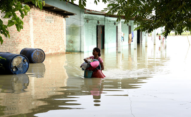 A woman carries her household belongings to a safer place in a flood-affected village of Kamrup district of Assam, India, on July 14, 2020. Villages in Assam were flooded due to heavy rains. The rising water level inundated houses, residents were forced to move to a safer place. (Photo by Hafiz Ahmed/Anadolu Agency via Getty Images)