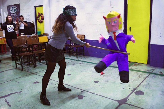 "A member of the organization ""Deportados Unidos en la Lucha"" – Deportees United in the Struggle – hits a pinata with the figure of US President Donald Trump during a traditional posada in Mexico City, on December 16, 2017. The Posadas is a Catholic ritual that reenacts Mary and Joseph's journey from Nazareth to Bethlehem in search of a birth place for the Christ Child. (Photo by Pedro Pardo/AFP Photo)"