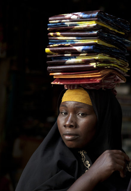 A cloth seller waits in hope of selling some pieces to a wholesale buyer, as sellers said their business was suffering following the recent coup, at the Grand Market in Bamako, Mali Saturday, March 31, 2012. (Photo by Rebecca Blackwell/AP Photo)