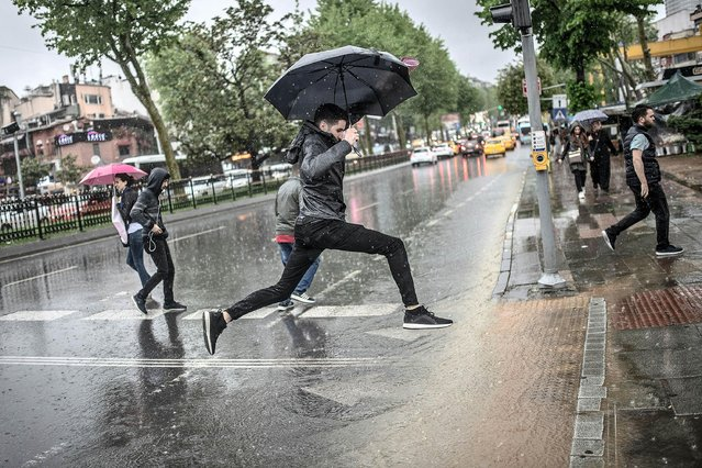 A man jumps over a large puddle at a pedestrian crossing during heavy rainfall in the Besiktas neighbourhood of Istanbul, on May 7, 2019. (Photo by Bulent Kilic/AFP Photo)