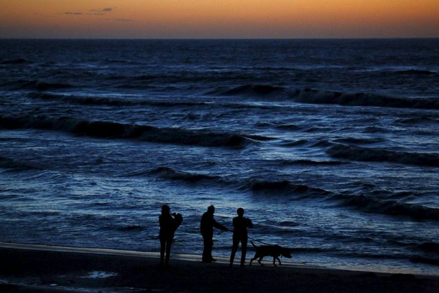 People walk with a dog on the beach after sunset at the Polish Baltic Sea coast near Choczewo, northern Poland August 17, 2015. (Photo by Kacper Pempel/Reuters)