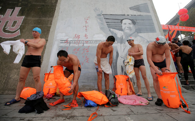 Winter swimmers put on clothes in front of a painting of late Chinese Chairman Mao Zedong after a swimming exercise in the Yangtze River to celebrate the 120th birth anniversary of Mao, in Wuhan, Hubei province December 26, 2013. (Photo by Reuters/Stringer)