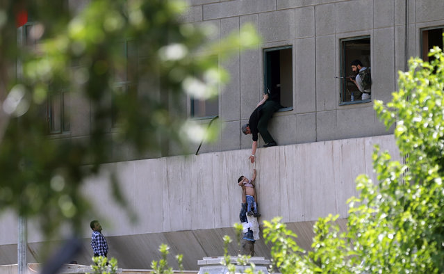 Iranian policemen try to help civilians fleeing from the parliament building during an attack in Tehran, Iran, 07 June 2017. At least seven people were killed and several others were wounded following twin attacks on Iran's parliament building and the mausoleum of former supreme leader, Ayatollah Khomeini, in the Iranian capital Tehran on 07 June, according to official sources. (Photo by Omid Wahabzadeh/EPA/EFE)