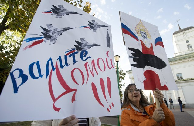 """Women hold placards during the opposition meeting against the deployment of Russian military bases in Minsk, Belarus, October 4, 2015. The sign reads, """"Go home"""". (Photo by Vasily Fedosenko/Reuters)"""