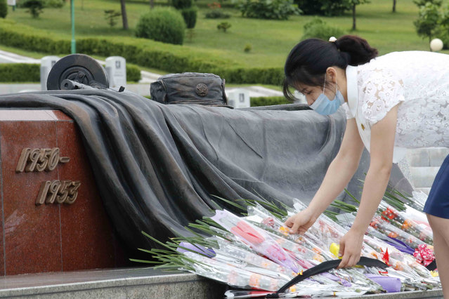 A North Korean woman lays a bouquet of flowers during a visit to the Fatherland Liberation War Martyrs Cemetery to pay respects to the monument to the fallen soldiers of the Korean People's Army in Pyongyang, North Korea, Thursday, June 25, 2020. (Photo by Jon Chol Jin/AP Photo)