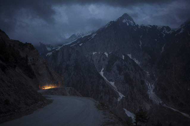 In this Monday, June 30, 2014 photo, a car moves on a serpentine road past snow-capped peaks near Zoji La in Indian-Kashmir, India. Many Tibetans say that being in the mountains make them miss their homeland. (Photo by Tsering Topgyal/AP Photo)