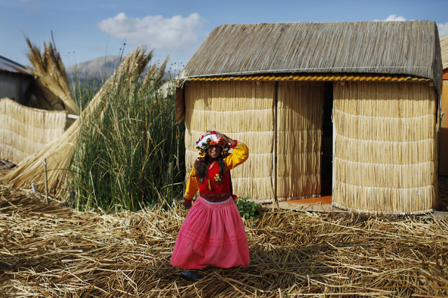 An Andean girl walks in front of her home, a straw hut, at a Uros island at Lake Titicaca in Puno November 5, 2014. (Photo by Enrique Castro-Mendivil/Reuters)