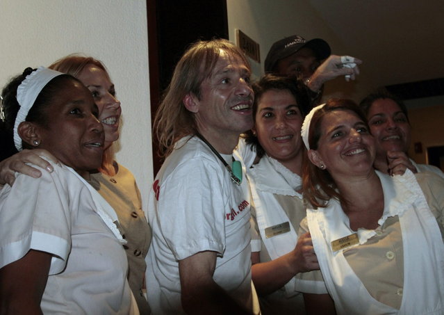 "Alain Robert of France, who is known as ""Spiderman"", poses with hotel employees after he climbed up the Habana Libre hotel in Havana February 4, 2013. Robert, who scales buildings all over the world without safety equipment, successfully climbed the hotel which is 126 metres (413 feet) high.  REUTERS/Stringer (CUBA - Tags: SOCIETY)"