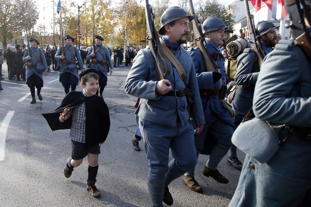"""Paul, 7, marches behind his father, a history enthusiast member of French association """"Le Poilu de la Marne"""", during an Armistice Day ceremony to commemorate the end of World War One at Epernay, eastern France, November 11, 2014. (Photo by Charles Platiau/Reuters)"""