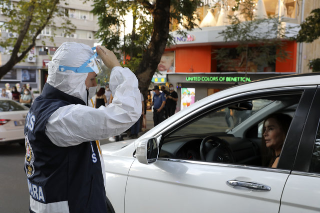A police officer wearing a face mask to protect against the spread of coronavirus, instructs a woman to wear her mask, in Ankara, Turkey, Thursday, August 6, 2020. Turkey's interior ministry announced new measures Wednesday to curb the spread of COVID-19 as daily confirmed cases peaked above 1,000. (Photo by Burhan Ozbilici/AP Photo)