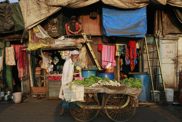 A vegetable seller pushes his cart at a slum area in Mumbai, India's financial capital and largest city, Tuesday, November 11, 2014. A whopping 41 percent of households in Mumbai were located in overcrowded shantytowns, where most residents are squatting illegally and many have little access to basic sanitation, according to a 2013 census report with India's first complete count of its vast slum population. (Photo by Rafiq Maqbool/AP Photo)