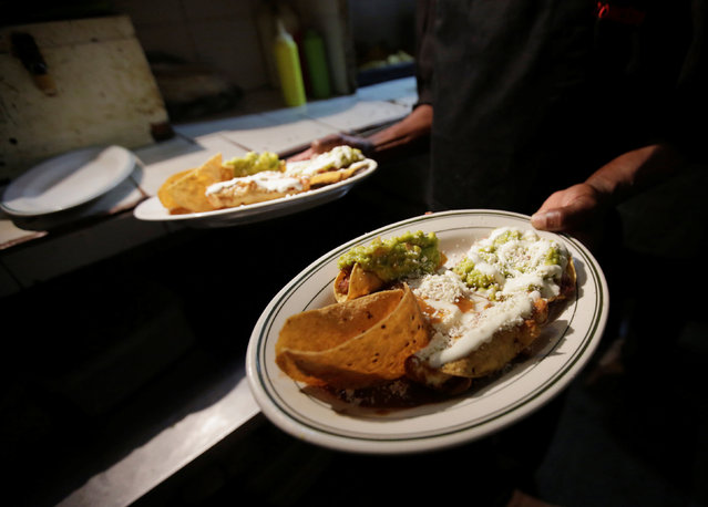 A chef of the El Tizoncito restaurant, shows dishes with Mexican foods while they offer this meal in exchange for two liters of cooking oil, in Caracas, Venezuela September 13, 2016. (Photo by Henry Romero/Reuters)