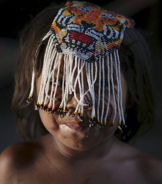 An indigenous girl from the Kamayura tribe jokes around with a handmade object inside her house in their village at Xingu national park in Mato Grosso, Brazil, October 2, 2015. (Photo by Paulo Whitaker/Reuters)
