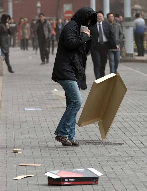 A woman covers her head while walking past a flying cardboard box after the capital city was hit by a sandstorm in Beijing Thursday, February 28, 2013. (Photo by Andy Wong/AP Photo)