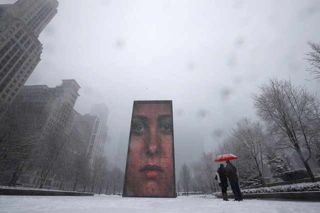 A couple takes pictures of an LED display on 50-ft tall glass towers, projecting images of faces in Crown Plaza during snow in Chicago March 5, 2013. A deadly late winter storm dumped heavy snow on the Midwestern United States on Tuesday, contributing to numerous highway crashes and flight cancellations as it moved east toward the Ohio Valley and the mid-Atlantic states.  (Photo by Jim Young/Reuters)
