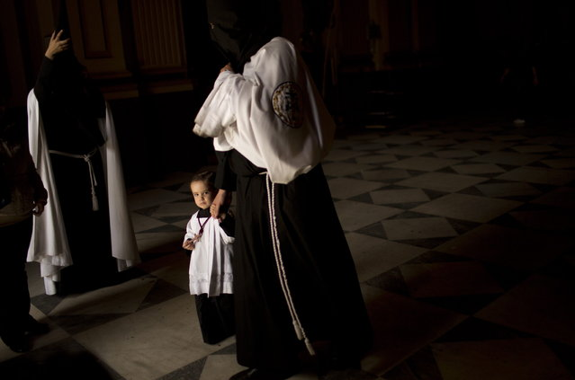 """Penitents from """"La Sed"""" brotherhood leave the church after the procession was cancelled due to bad weather in Seville, Spain, Wednesday, March 27, 2013. Most of the  Eater Holy Week processions were canceled in Seville because of the rain Wednesday. (Photo by Emilio Morenatti/AP Photo)"""