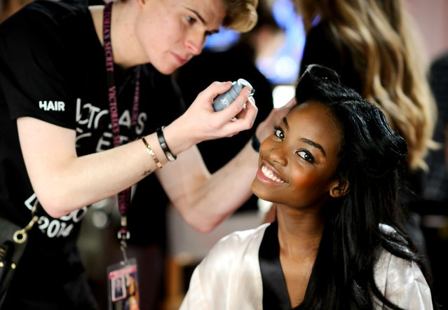 Angolan model Maria Borges gets her hair done backstage ahead of the 2014 Victoria's Secret Fashion Show at Earl's Court Exhibition Centre in London on December 2, 2014. (Photo by Leon Neal/AFP Photo)