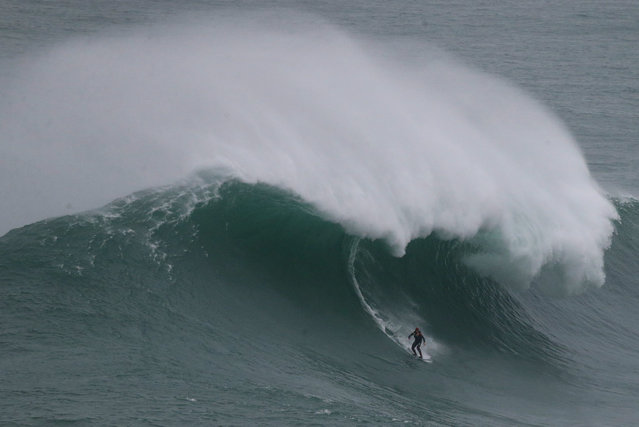 A surfer rides a big wave during a tow-in surfing session at the Praia do Norte, or North beach, in Nazare, Portugal, Sunday, November 1, 2015. US surfer Garrett McNamara set a world record for the largest wave surfed when he rode a 23.7 metre wave (78-foot) in Nazare in 2011. (Photo by Armando Franca/AP Photo)